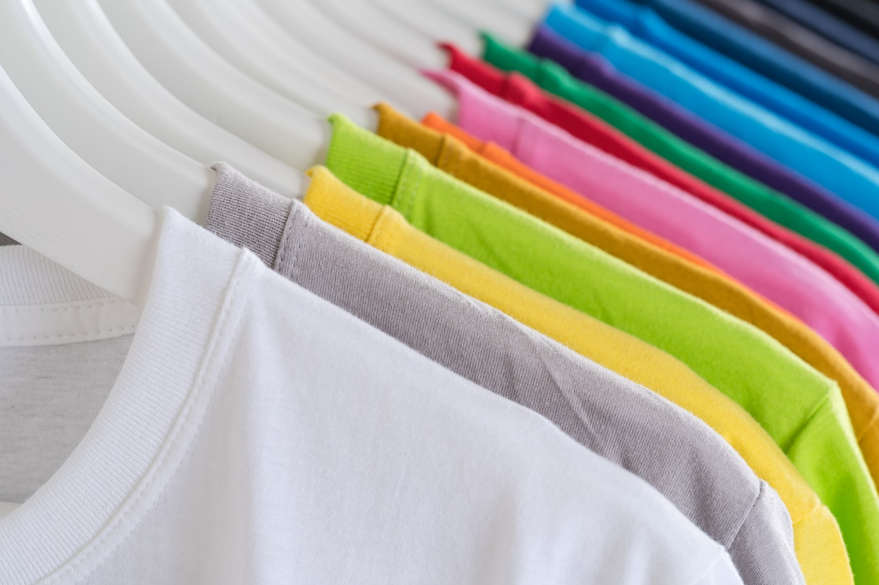 T-shirts hanging on a rack in different colors